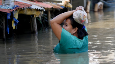 A resident wades through floodwaters after buying basic food items for dinner following flooding brought about by Typhoon Mangkhut which barrelled into northeastern Philippines .
