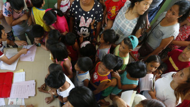 Children and their parents queue in Manila, Philippines, to have their children vaccinated following an outbreak of measles.