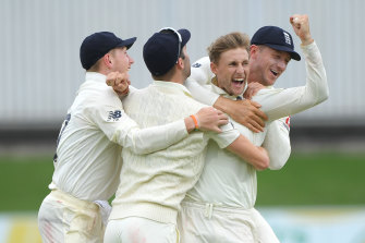 Joe Root is swamped by teammates after taking the wicket of Rassie van der Dussen.