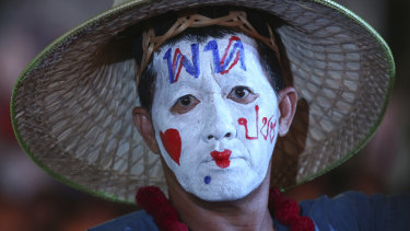 "A supporter of Pheu Thai Party wears a message on his head reading ""Pheu Thai Party love people"" during an election campaign in Bangkok on Friday."