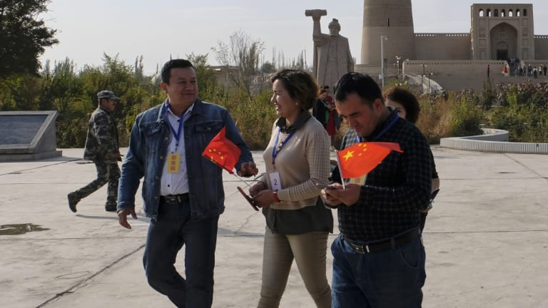Chinese national flags on the hands of minorities who are on a patriotic tour to Ermin Minaret in Turpan City, Xinjiang Uyghur Autonomous Region, China last month.