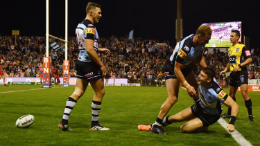 Hero of the day: teammates mob Bronson Xerrri after one of his three tries for Cronulla.