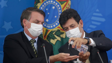 Mixed messages. President Jair Bolsonaro and Health Minister Luiz Henrique Mandetta on March 18.