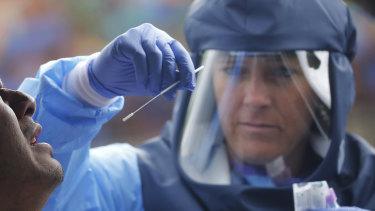 Salt Lake County Health Department public health nurse Lee Cherie Booth performs a coronavirus test outside the Salt Lake County Health Department in Salt Lake City.