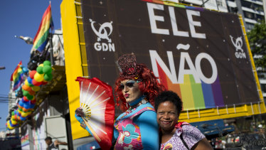 """A woman and a drag queen pose for a photo backdropped by a billboard with a message that reads in Portuguese: """"Not Him"""", in reference to presidential candidate Jair Bolsonaro. Bolsonaro has a long history of offensive comments about gays, women and minorities."""