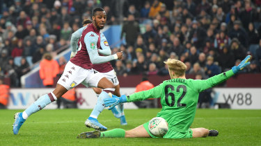 Jonathan Kodija of Aston Villa guides the ball past Caoimhin Kelleher of Liverpool for his team's third goal  at Villa Park.