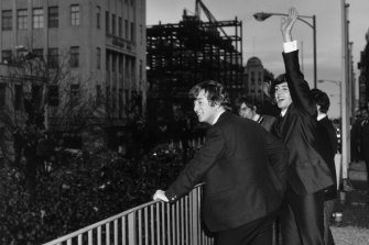 The Beatles wave to the fans from the first floor balcony of the Southern Cross Hotel, Melbourne.