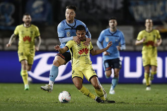 Sydney FC's Alex Baumjohann tackles Wellington Phoenix star Ulises Davila in last week's A-League restart.