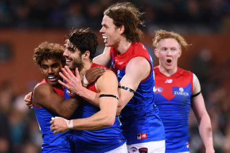 Christian Petracca celebrates one of his three goals with Kysaiah Pickett, who also kicked three goals, and Ben Brown.