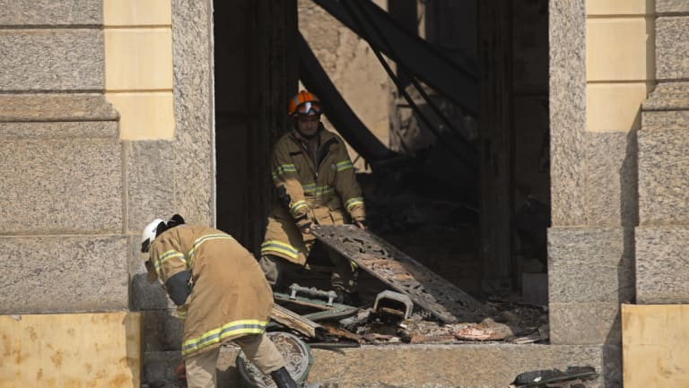 Firefighters removed remnants of artifacts and paintings that survived the fire.