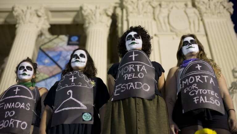 """Pro-choice demonstrators wear signs that say in Portuguese: """"Death by abortion"""" to protest against the deaths of women who died after illegal abortions."""