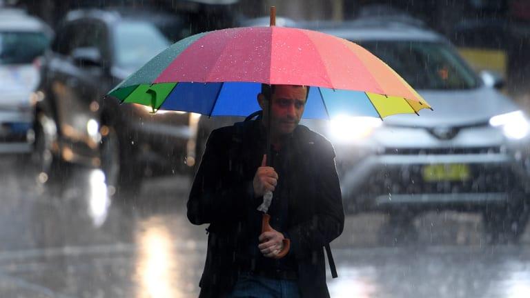 Pedestrians brave heavy rain on Friday afternoon.