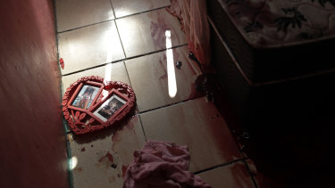 Blood covers the floor and a picture frame in a shape of a heart, inside a home during a police raid targeting drug traffickers in the Jacarezinho favela of Rio de Janeiro.