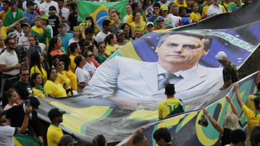Supporters of Brazil's new President Jair Bolsonaro display a giant banner of him on his inauguration day in Brasilia, Brazil.