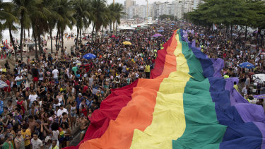 """People carry a giant rainbow banner in Rio during a Gay Pride parade under the theme """"Vote in ideas and not in people,"""" which aims to encourage people to vote for candidates who support gay and human rights."""