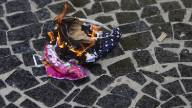 Protective masks are burned by supporters of Brazilian President Bolsonaro during a rally in favour of Bolsonaro's position that no one will be forced to use them and eventually get a coronavirus vaccine in Rio de Janeiro.