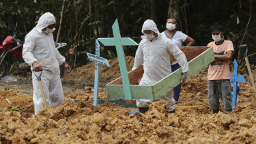 Funeral workers in protective gear prepare a grave at a Manaus cemetery, for a woman who is suspected to have died of COVID-19.