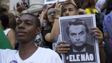 """People protest holding signs with a message that reads in Portuguese: """"Not him"""" during a protest against Jair Bolsonaro."""