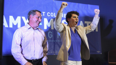 Amy McGrath, right, with her husband, Erik Henderson, pumps her fists after being elected as the Democratic candidate for Kentucky's 6th Congressional District.
