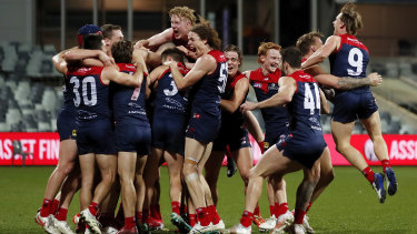 The Demons celebrate taking out the minor premiership at Geelong.