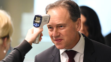 Federal Health Minister Greg Hunt, having his temperature checked before touring the Royal Melbourne Hospital, has delayed the vaping nicotine ban.