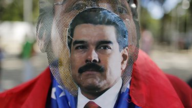 A pro-government protester wears a make-shift mask with an image of President Nicolas Maduro taped to it in Caracas.