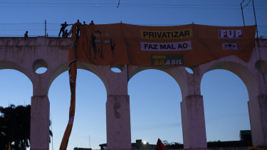 "Oil workers hang a banner that reads in Portuguese ""Privatisation hurts Brazil"" during a protest against layoffs at the oil giant Petrobras in Rio de Janeiro."