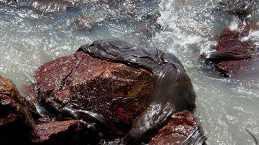 Oil sludge covers a rock at the Coroa do Meio beach, in Sergipe, state, Brazil.
