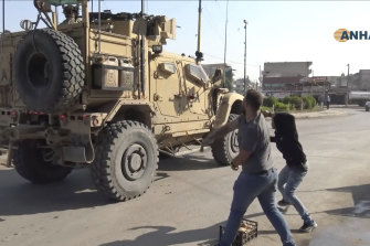 Residents angry over the US withdrawal from Syria hurl potatoes at American military vehicles.