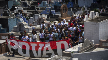 "Friends and relatives of Christian Candido carry a banner that reads ""People"" in Portuguese during his funeral procession in a Rio de Janeiro cemetery."