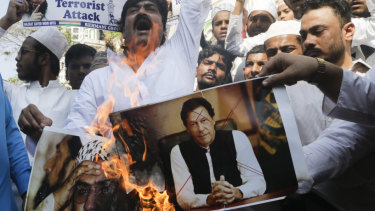 Indian muslims burn posters of Pakistani Prime Minister Imran Khan, centre, and Hafiz Saeed, chief of Pakistani religious group Jamaat-ud-Dawa, during a protest against Thursday's attack on a paramilitary convoy.