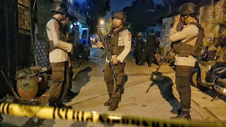 Armed police at a site where a suspected terrorist was shot dead and four members of his family apprehended after the Surabaya attacks.