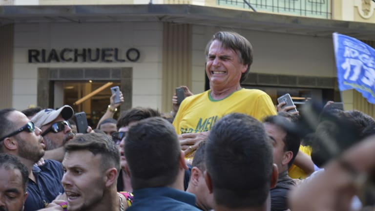 Brazilian presidential candidate Jair Bolsonaro grimaces after being stabbed.