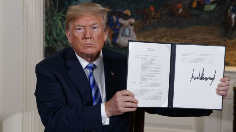 President Donald Trump shows a signed memorandum confirming the US withdrawal from the Iran nuclear deal.