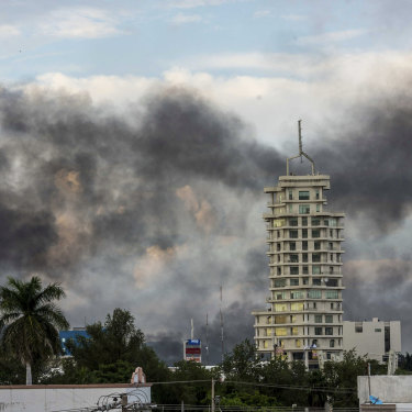 Smoke from burning cars in Caliacun as cartel members attempt to force the government to free a drug lord.