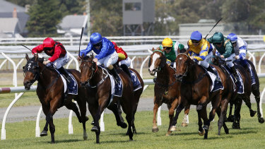 Asiago, in the blue colours of Godolphin, pulls away from Rule The World at the 200m mark.