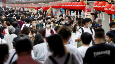People wearing face masks pack in a shopping arcade of Asakusa district in Tokyo Sunday, Sept. 20, 2020.