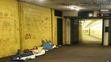 Two homeless people sleep near the entrance to St James railway station.