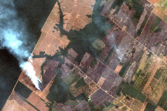 A satellite photo of the upper Amazon River basin burning on August 15. Cleared pastoral land is clearly visible in various degrees of deforestation compared with the forest (left of screen).