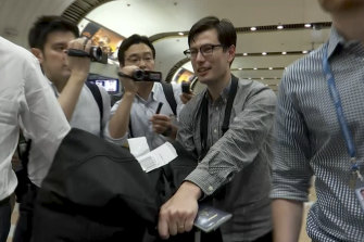 Australian student Alex Sigley walks through journalists as he arrives at the airport in Beijing