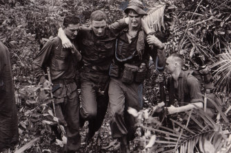 An Australian infantryman injured in a boobytrap bomb blast is helped to an evacuation helicopter  by fellow members Charlie Company, 5thb Royal Australian Regiment in November 1966. Peter Yule's book examines the experience of Vietnam veterans in Australia.