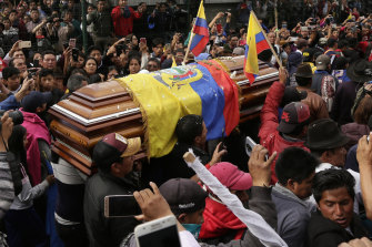 Anti-government protesters carry a coffin containing the remains of indigenous leader Inocencio Tucumbi, who protesters say died during the country's unrest.