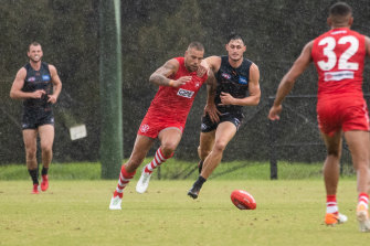 GWS defender Jake Stein trails Lance Franklin as he attacks a loose ball on Sunday morning.