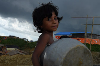 Storm clouds hang overhead as a Rohingya child carried a pot in Kutupalong camp last year.