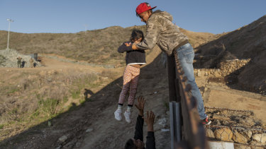 A migrant from Honduras pass a child to her father after he jumped the border fence to get into the US side to San Diego, California, from Tijuana, Mexico.