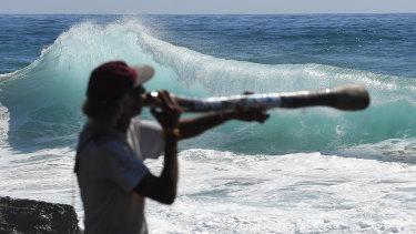 Local Russell Corowa playing the didgeridoo at Snapper Rocks on the Gold Coast, while huge swells and high tides are set to pummel south-east Queensland beaches over the coming days.