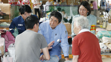 Japanese PM Shinzo Abe listens to an evacuee during a visit to an evacuation center in Kurashiki.