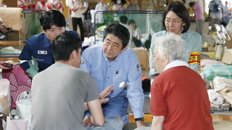 Japanese PM Shinzo Abe listens to an evacuee during a visit to an evacuation center in Kurashiki.