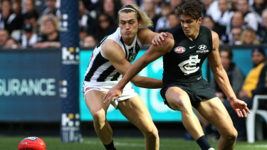 Darcy Moore of the Magpies, left, takes on Charlie Curnow of the Blues.