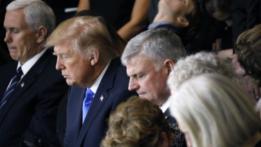 Franklin Graham (centre) and the Graham family pray alongside US President Donald Trump and Vice-President Mike Pence as Billy Graham lies in honour at the US Capitol in February 2018.